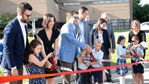 Large group of people cutting ribbon with large scissors