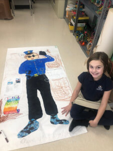 Ivywood student sitting next to her life size drawing of a police officer