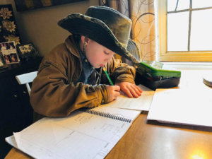 Student in a cowboy hat working at a table on school work